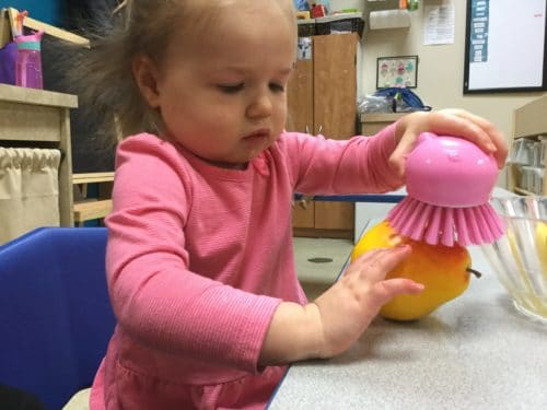 a toddler girl using a pink scrubber to wash a pear
