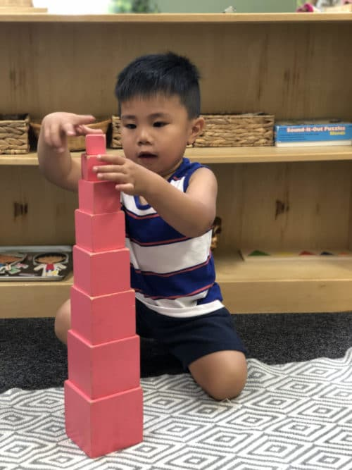 a young boy stacking a tower using pink blocks